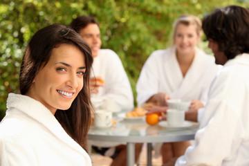 Woman enjoying breakfast outdoors with friends