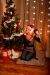 Interested girl near Christmas tree shaking present box