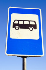Bus stop road sign on background of blue sky.