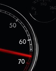 Car tachometer, dash board close up, red arrow in a red zone