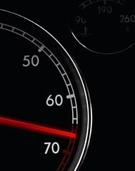 Car tachometer, dash board close up, red arrow in a red zone