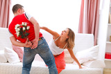 Husband hiding flowers from his curious pregnant wife