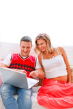 Happy man showing his pregnant wife something in laptop