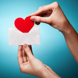 woman's hand holding an envelope with a sign of the heart agains