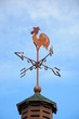 Wind cock weather vane direction on blue sky