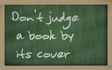 """"""" Don't judge a book by its cover """" written on a blackboard"""