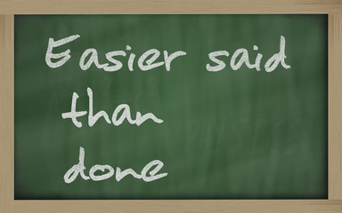 """ Easier said than done "" written on a blackboard"