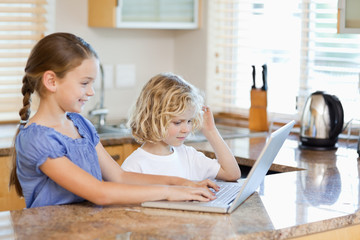Siblings on the laptop in the kitchen