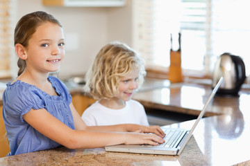 Siblings with laptop behind the kitchen counter