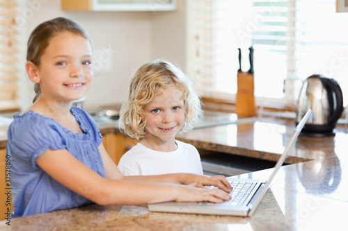 Smiling siblings on the laptop in the kitchen