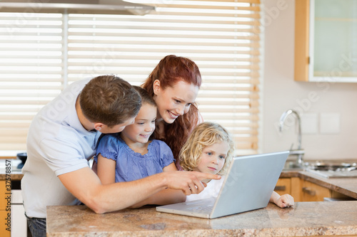 Family with laptop in the kitchen