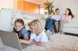 Siblings using laptop in the living room