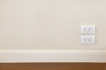 Wall with wooden floor and power outlet