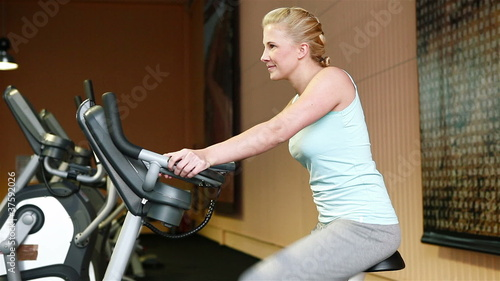 Woman using hometrainer in fitness center