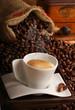 Caffè italiano in  tazza bianca e chicchi tostati sullo sfondo
