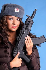 Beautiful young Russian woman holding an AK47 automatic rifle.