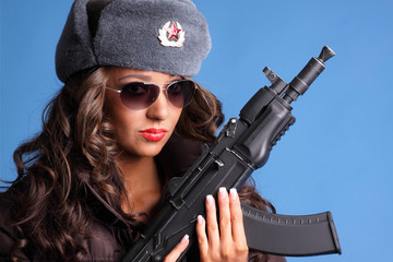 Beautiful young Russian woman holding an AK47 automatic rifle.