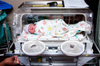 Cute sick baby in incubator