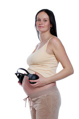Pregnant woman with headphones on stomach.