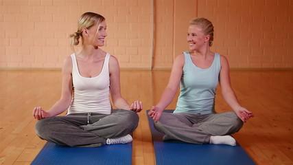 Two girls meditating in gym