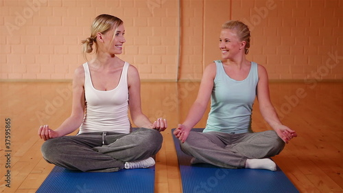 Two girls meditating in gym