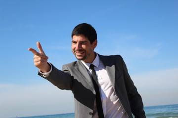 A young businessman pointing his hand like a gun
