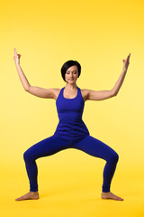 Young woman in blue doing yoga asana on yellow