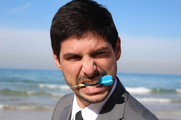 Young handsome businessman with a blue dart in his mouth