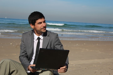Businessman with laptop sitting at the beach