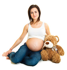 Brunette pregnant woman with teddy bear isolated on white