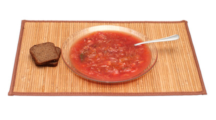 Plate with a borsch and rye bread on a bamboo mat.