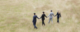 Business people holding hands walking in field