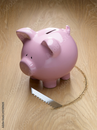 Saw cutting a hole around a piggy bank