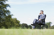 Businessman sitting in chair talking on cell phone outdoors