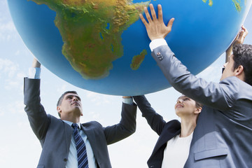 Business people holding up large ball together