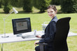 Businesswoman sitting at desk in field