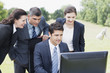 Business people using computer together outdoors