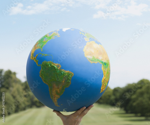 Hand holding large globe outdoors