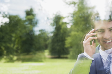 Businessman standing behind glass talking on cell phone