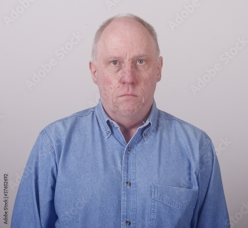 Older Balding Man in Blue Denim Looking Serious