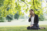 Businesswoman sitting in grass talking on cell phone