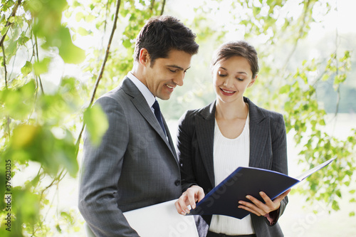 Business people looking at report together outdoors