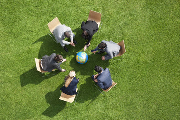 Business people having meeting outdoors looking at globe