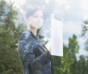 Businesswoman holding paper against window