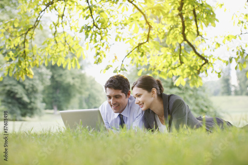 Business people laying in grass using laptop