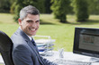 Businessman sitting outdoors at desk