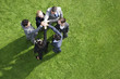 Business people standing in circle holding hands