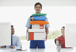 Deliveryman holding stack of packages in office