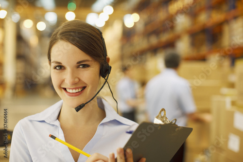 Woman in headset holding clipboard in warehouse