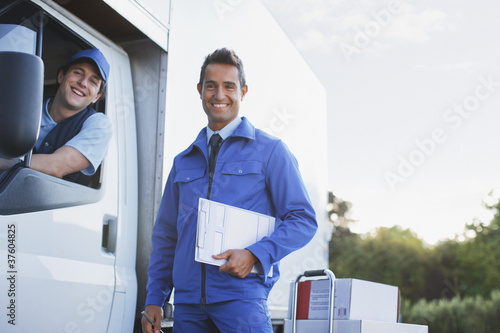 Worker standing outdoors with delivery driver